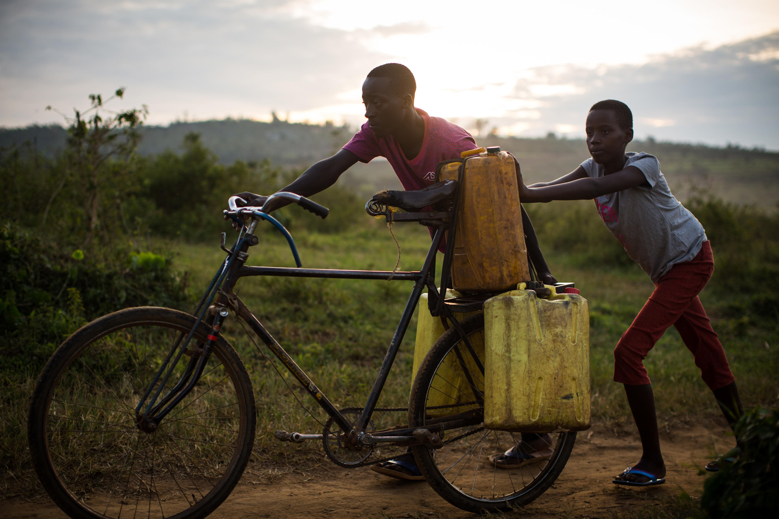 Jean-Bosco and Claire push their bike, now laden with jerry can's of water, back home, Rwanda.