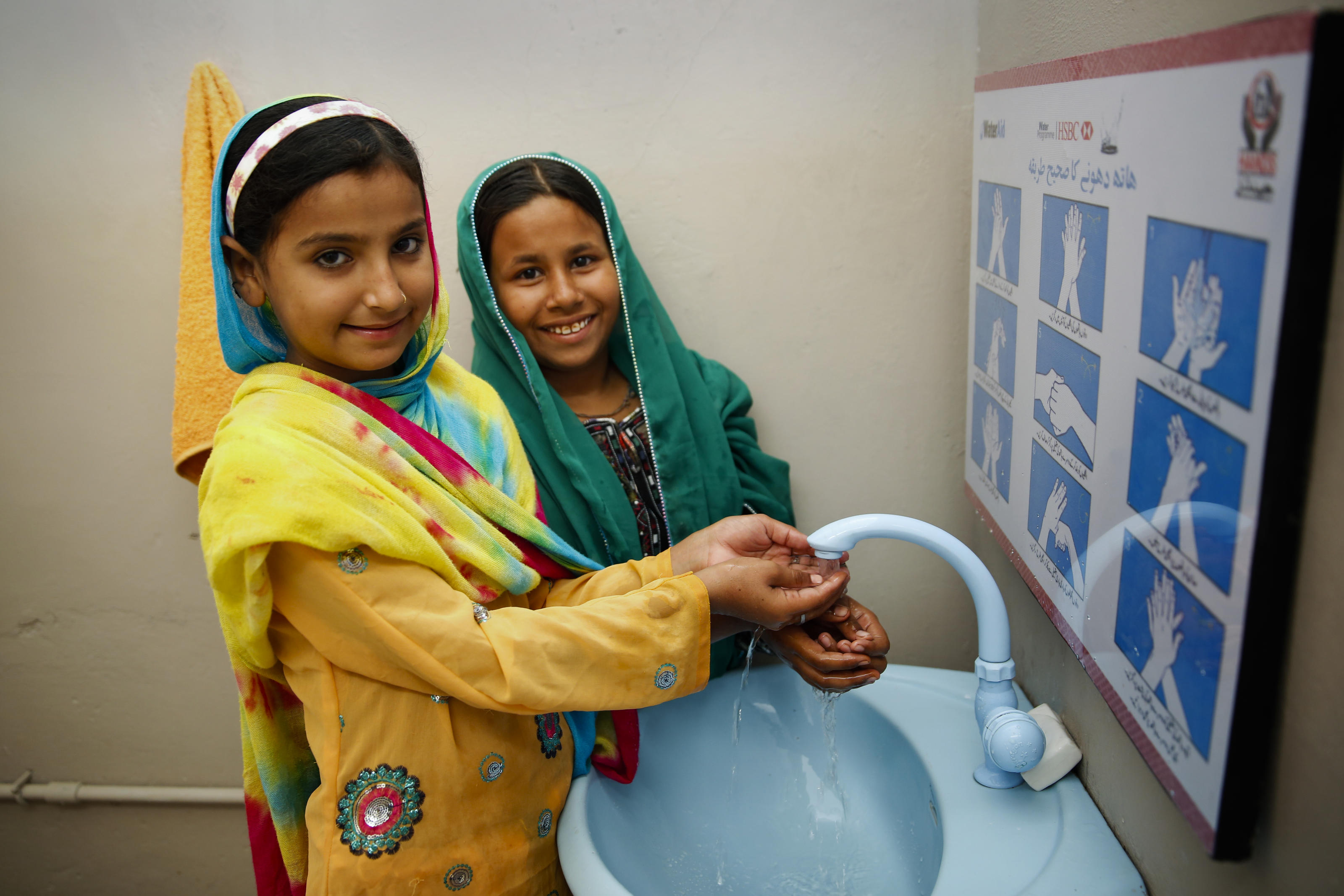 Shazia and Nadia washing their hands with soap at a tap in a newly installed facility in their school in Pakistan