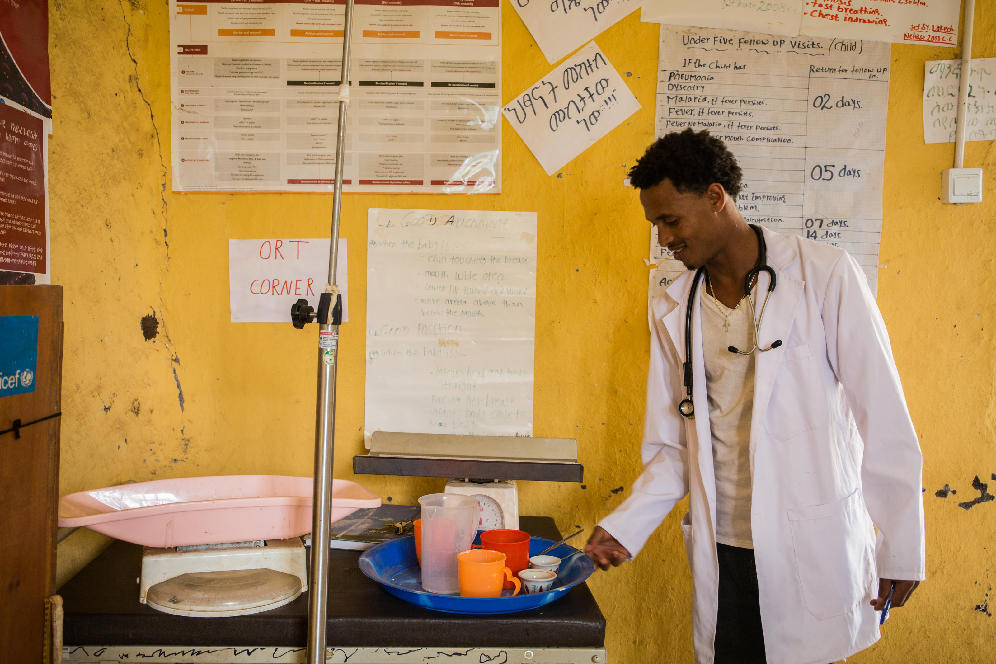 Yaye Wale, 25, a clinical nurse, standing with a cup of water and Oral Rehydration Therapy (ORS) he uses to demonstrate for parents whose children have diarrhea, Yiraber Health Centre, Ethiopia