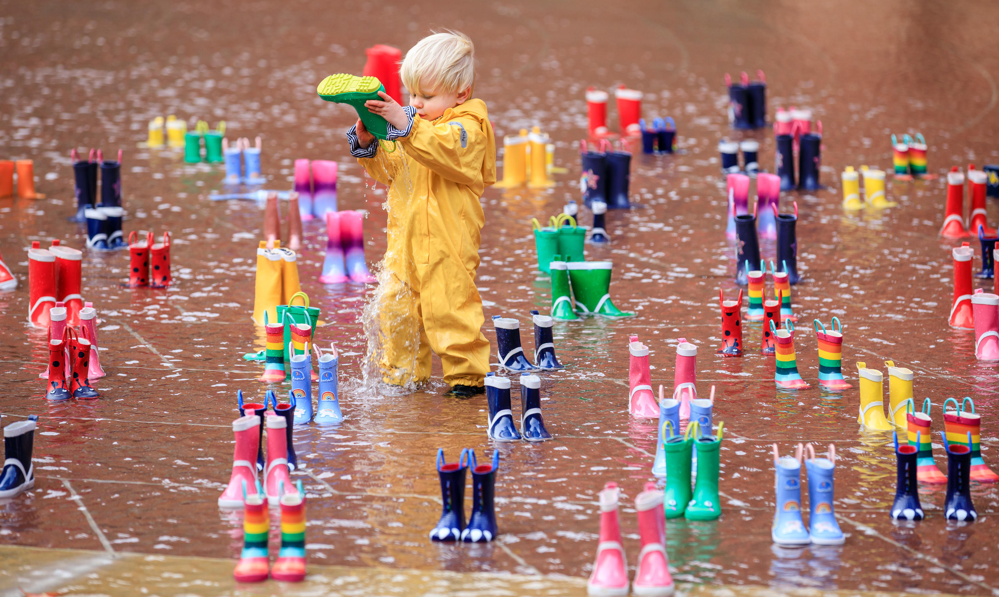 Puddles are for splashing in, not drinking: Archie, 2, from London admires 144 pairs of brightly coloured wellies, laid out by WaterAid in the garden of London's V&A to highlight the 144 million children, women and men worldwide who rely on surface wa ...