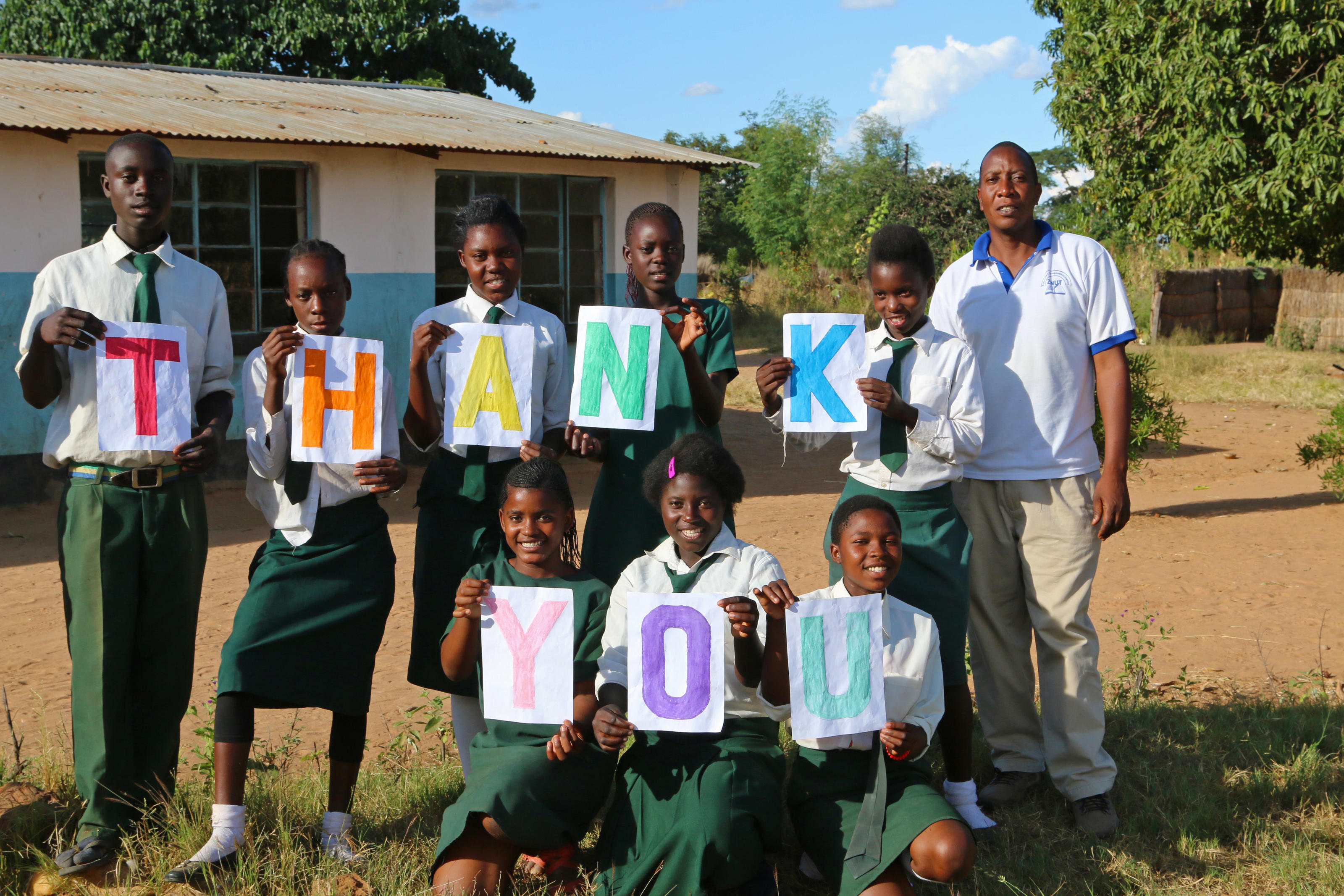 Pupils and their Head Teacher display a 'Thank you' sign for the piped water system that was recently installed at their school.
