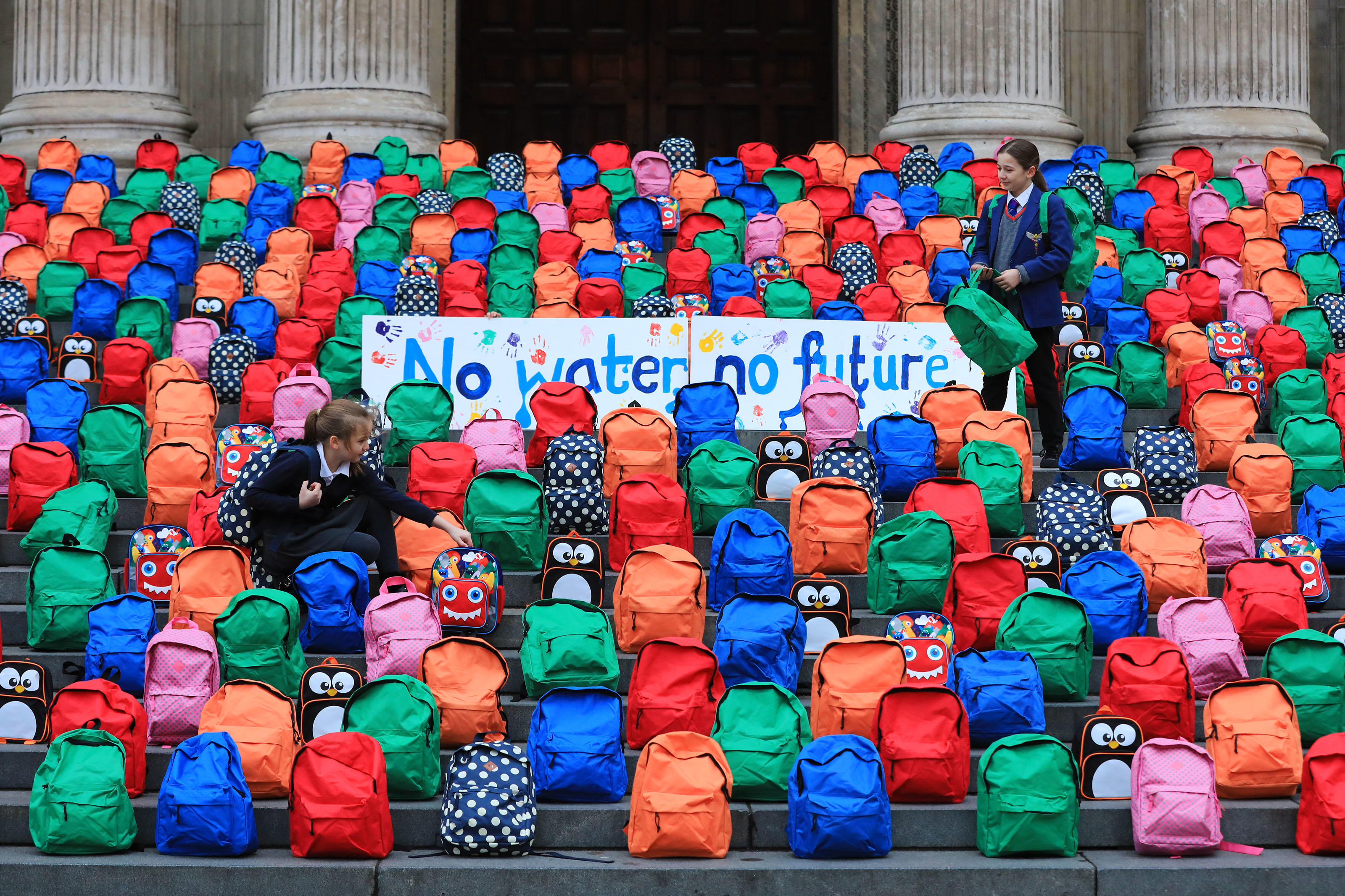 Schoolchildren Joana and Jessica look at the 800 schoolbags laid by WaterAid on the steps of St Paul's Cathedral