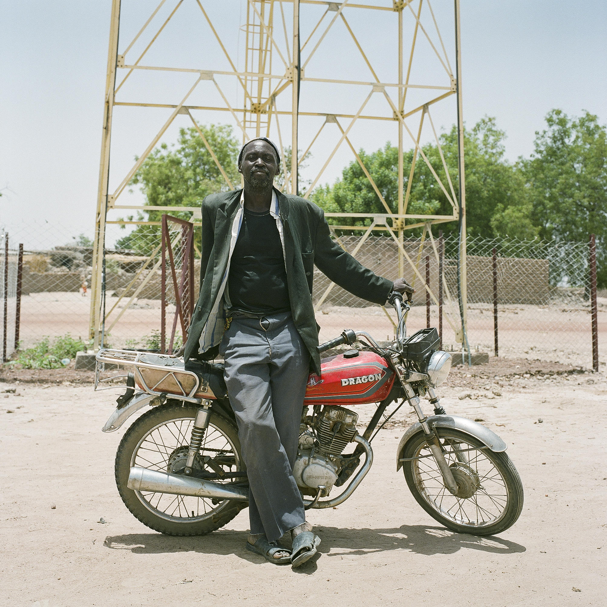 Souleymane Diallo, a trainee water mechanic stands against his motorcycle in Samabogo, Mali.