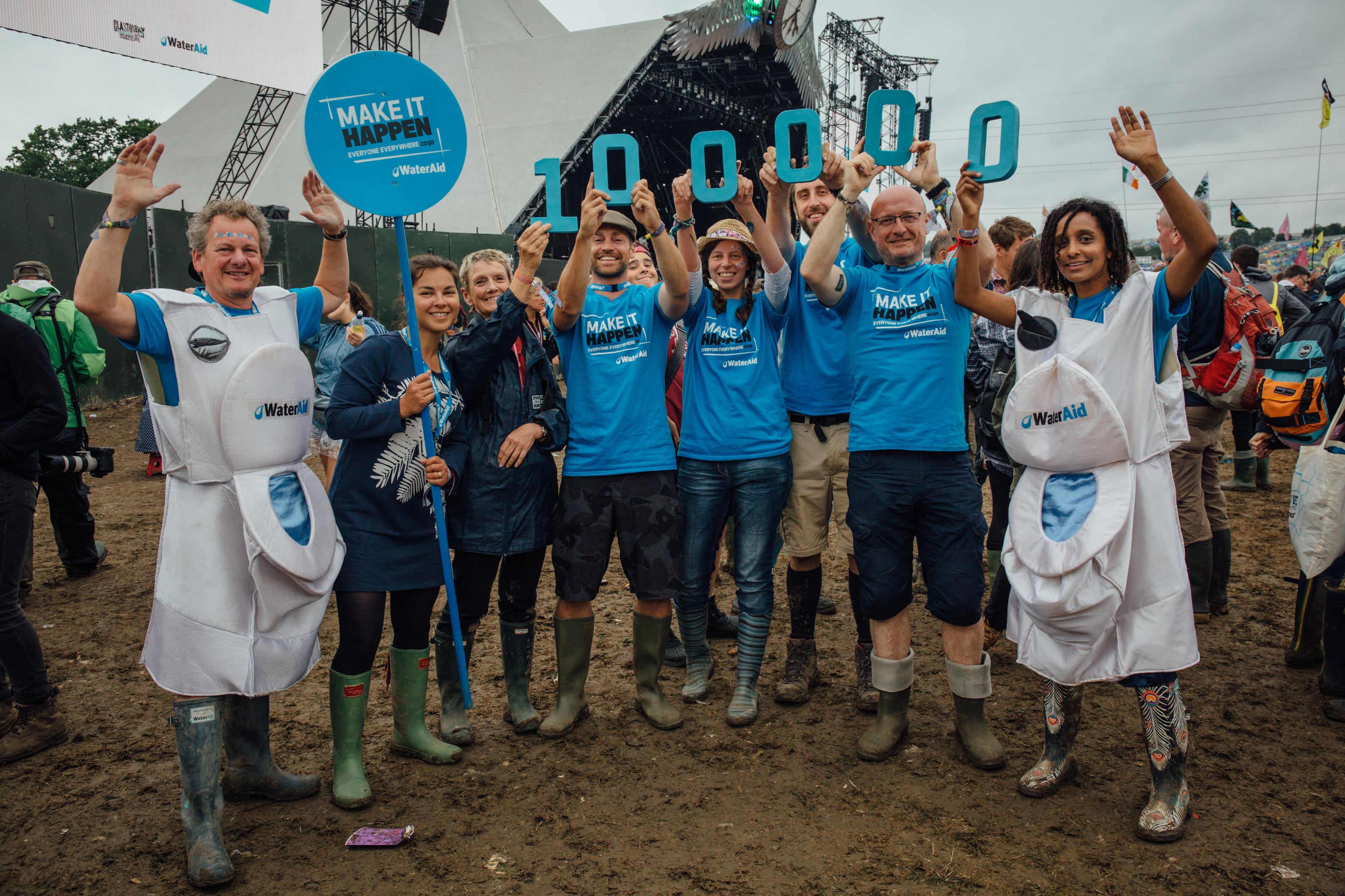 WaterAid staff at Glastonbury 2015, celebrating the 100000 signatures signed for our petition.