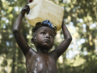 Ibrahim (Haja's son) carries a container of dirty water on his head on his way home.