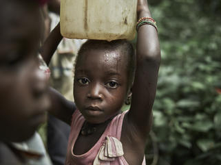 Nancy, carrying a container, called a 'gallon' of dirty water collected from a natural water.