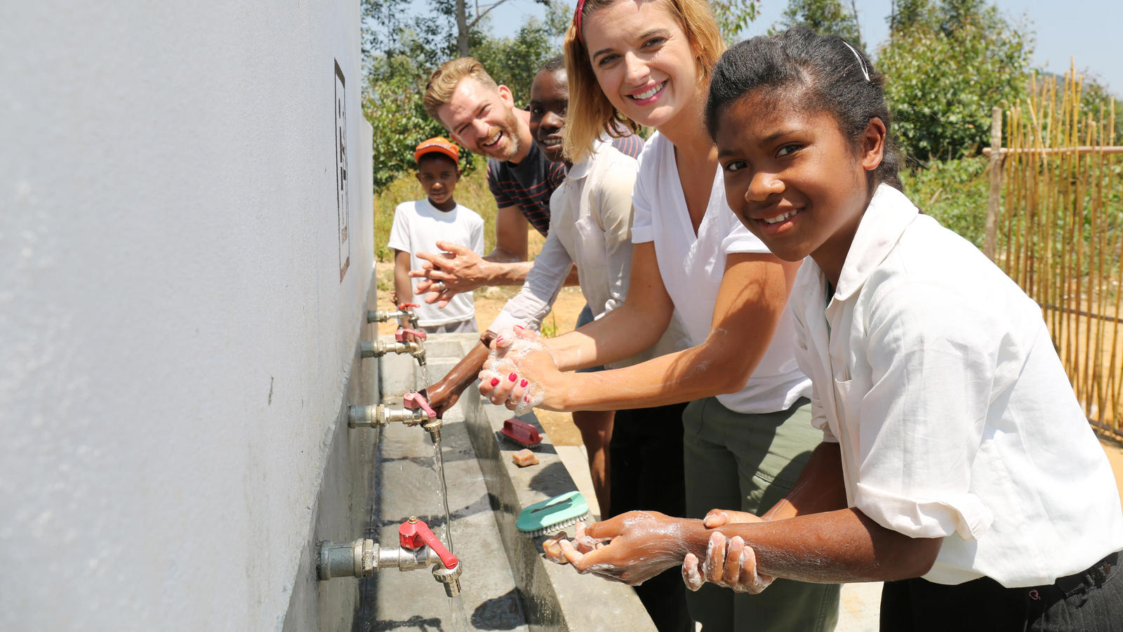 Simon and Clemmie Hooper, with Tahina, 13, and students, washing their hands in Moramanga, Madagascar.