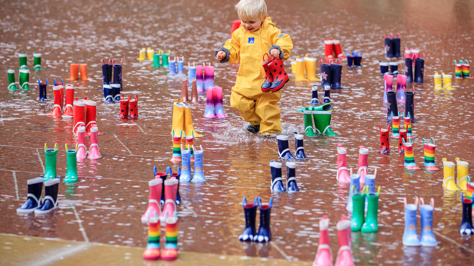 2-year-old Archie from London admires 144 pairs of brightly coloured wellies and splashes in the pond in the garden of London's V&A