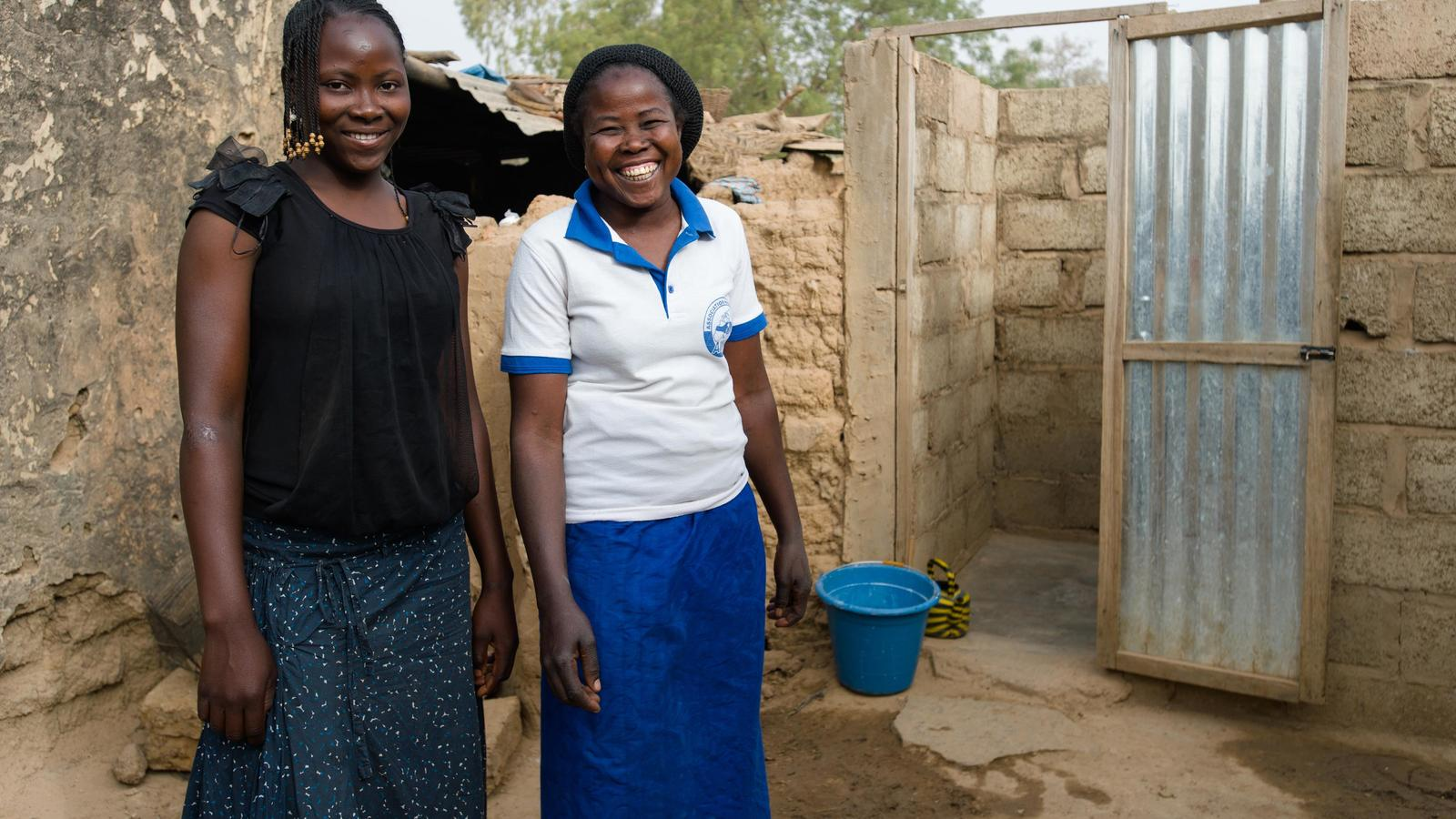 Fati and her daughter Safiatou outside the toilet at their home in Zongo, Burkina Faso.