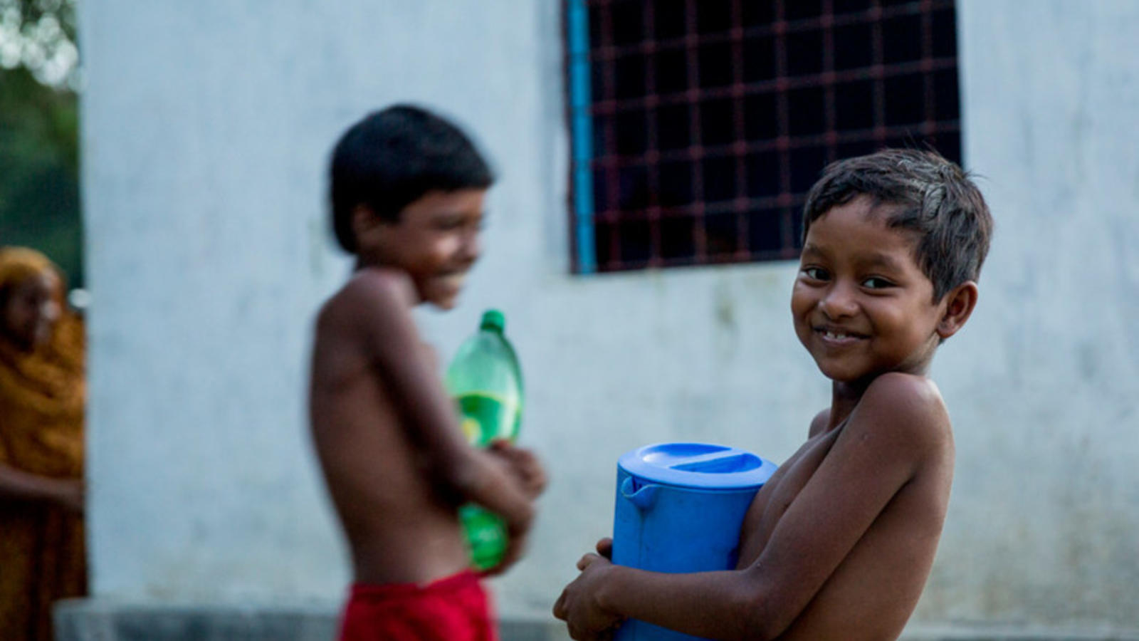 Two young boys carrying water containers and smiling.