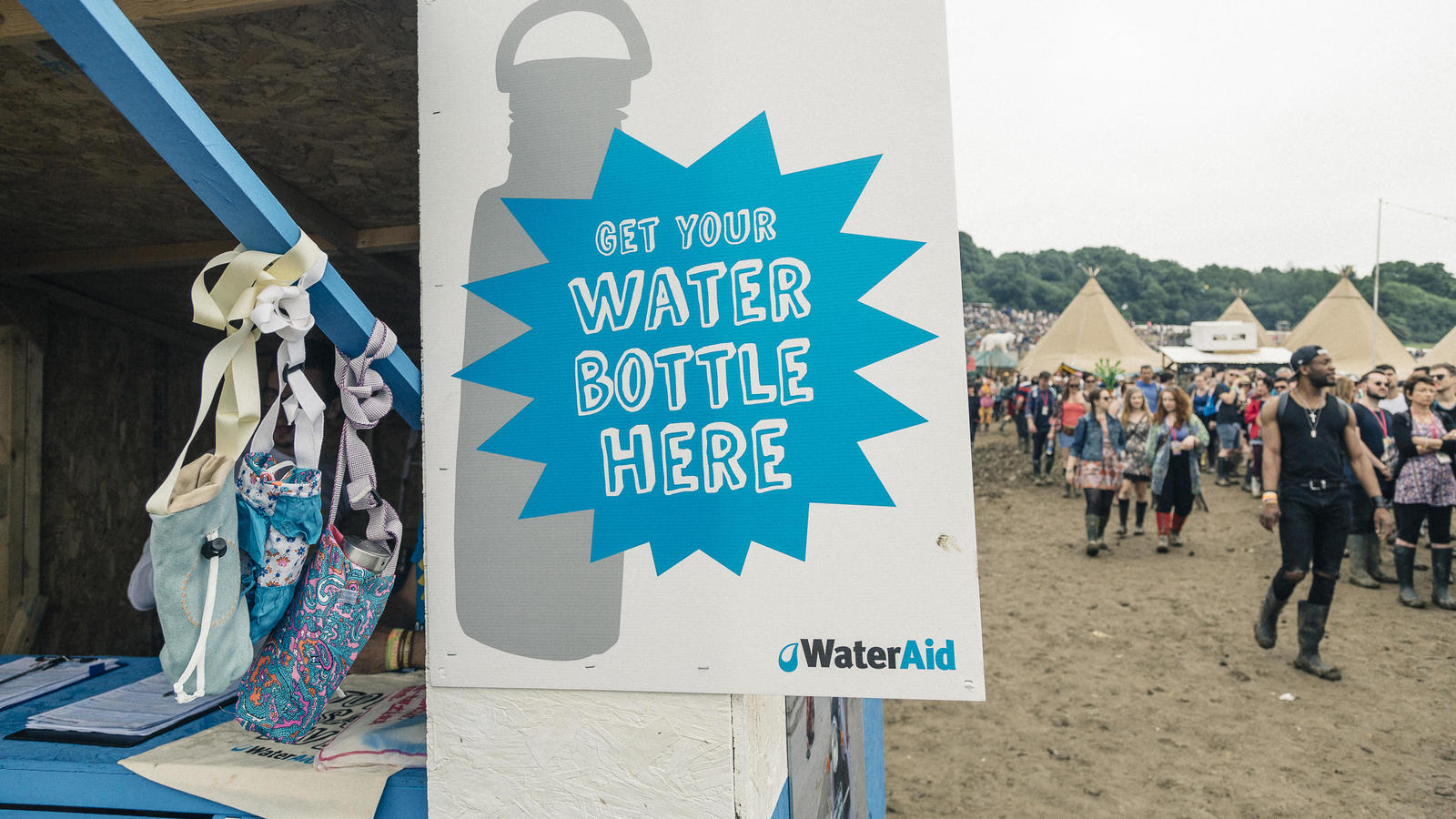 A sign lets festivalgoers know that they can pick up preordered official Glastonbury Festival Water Bottles at a WaterAid kiosk, or buy one for £10.