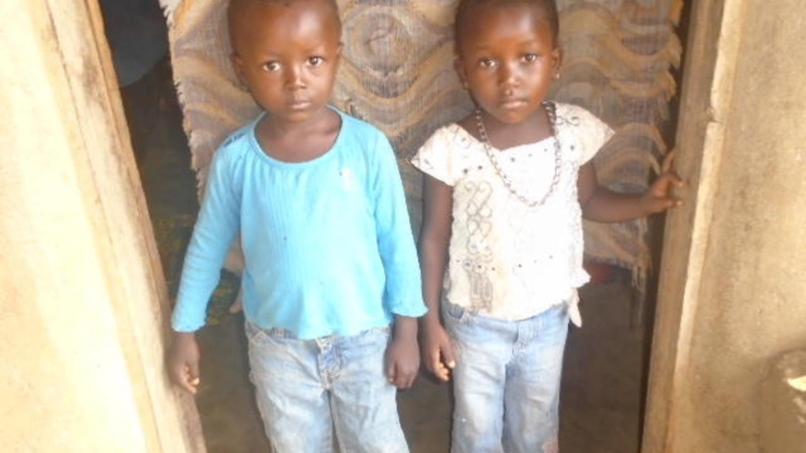 Two of Haja's surviving children, dressed and ready for school.