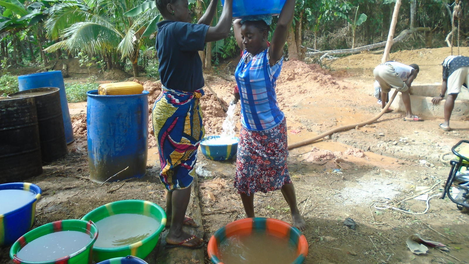 Sellu's sister and wife Fatu fetching the first water that came out from the well.
