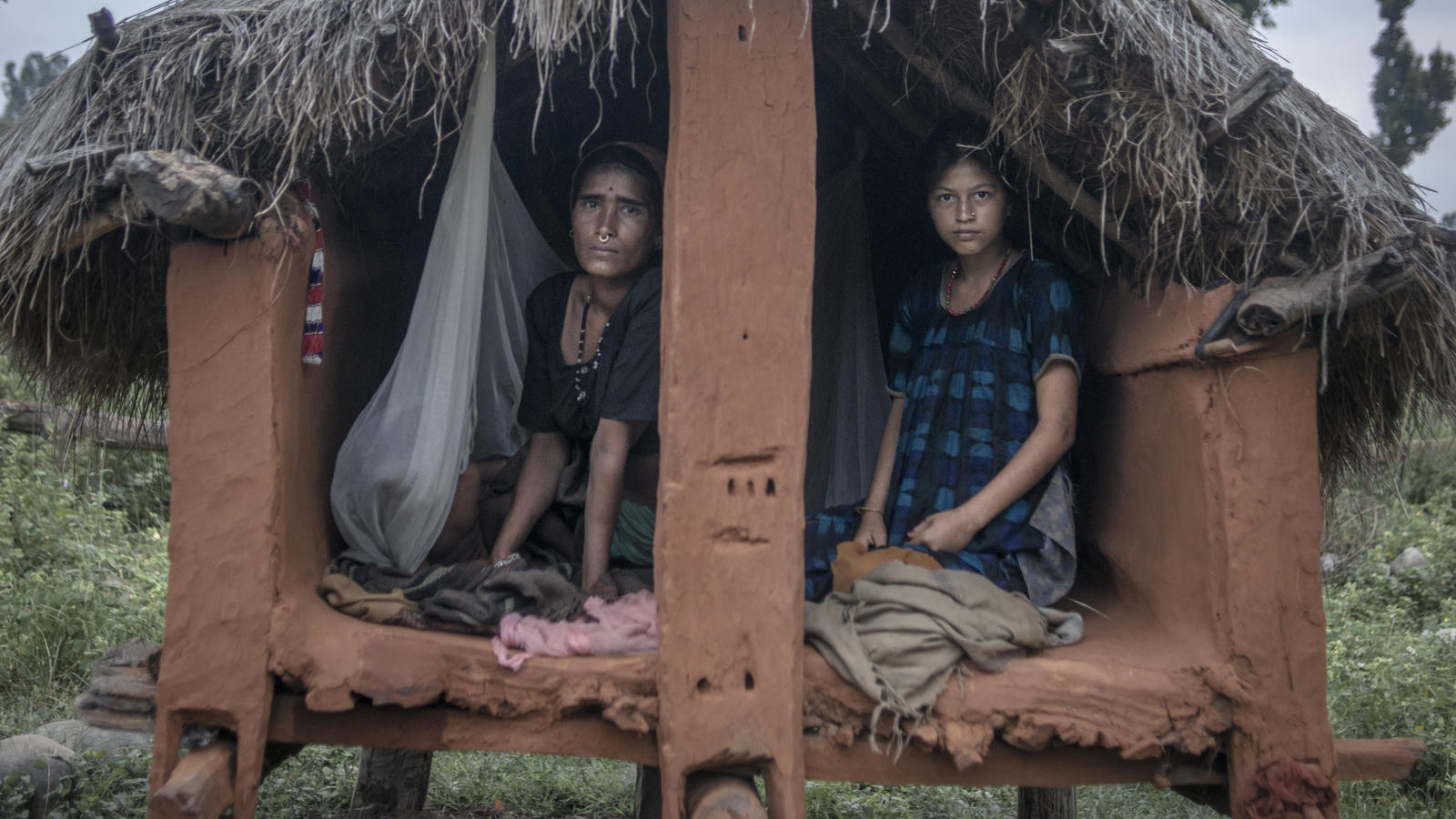 Mangu and Chandra prepare to spend the night in a chhaupadi hut. Being together offers some protection against the risk of sexual assault and rape, but not against snake attacks.