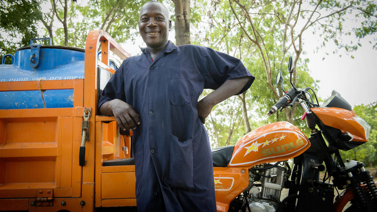 Julius stands next to one of the vehicles that transports gulper pump equipment in Dar es Salaam City, Tanzania.