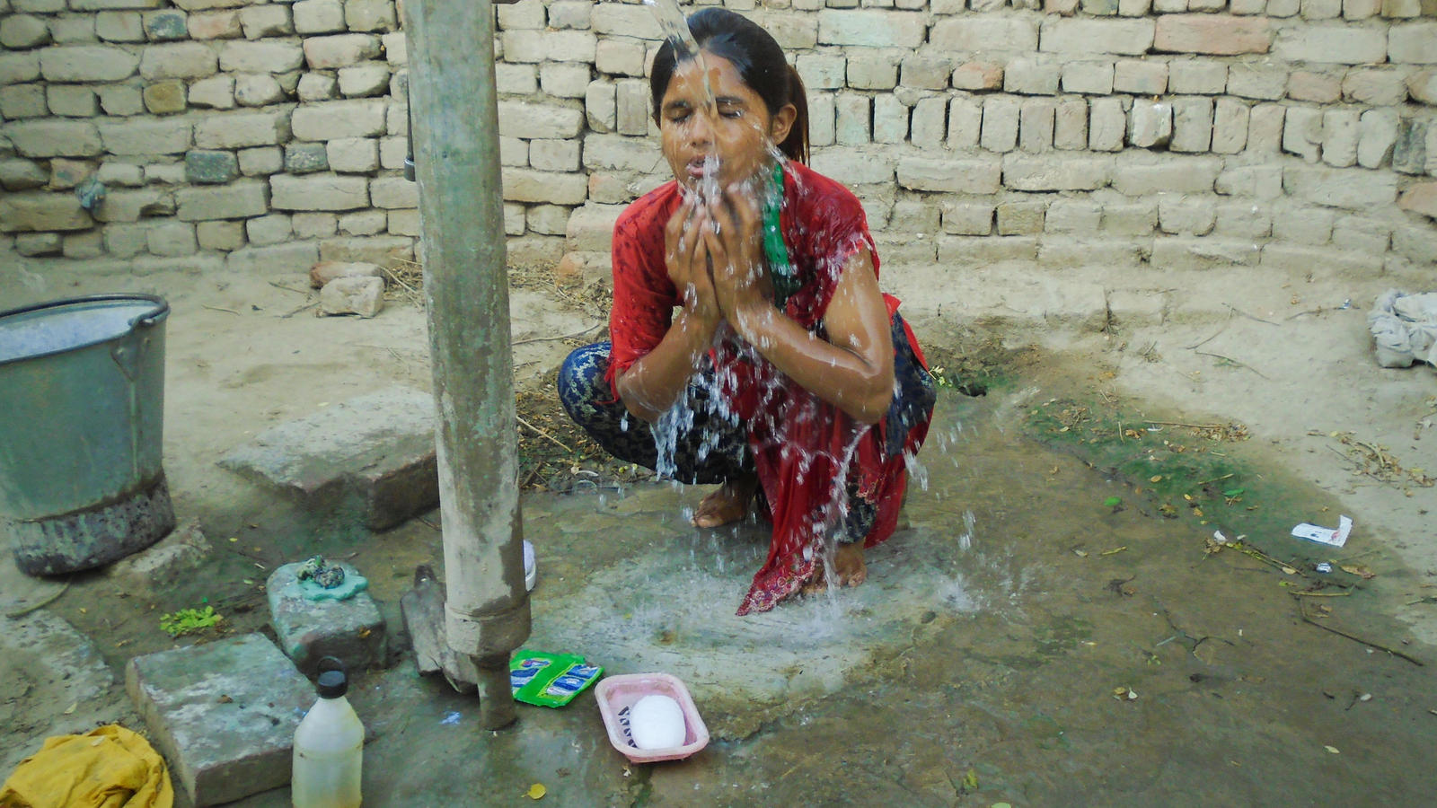 Gulshan, 9, washing her face in her home in the village of Waan Pitafi, Pakistan.