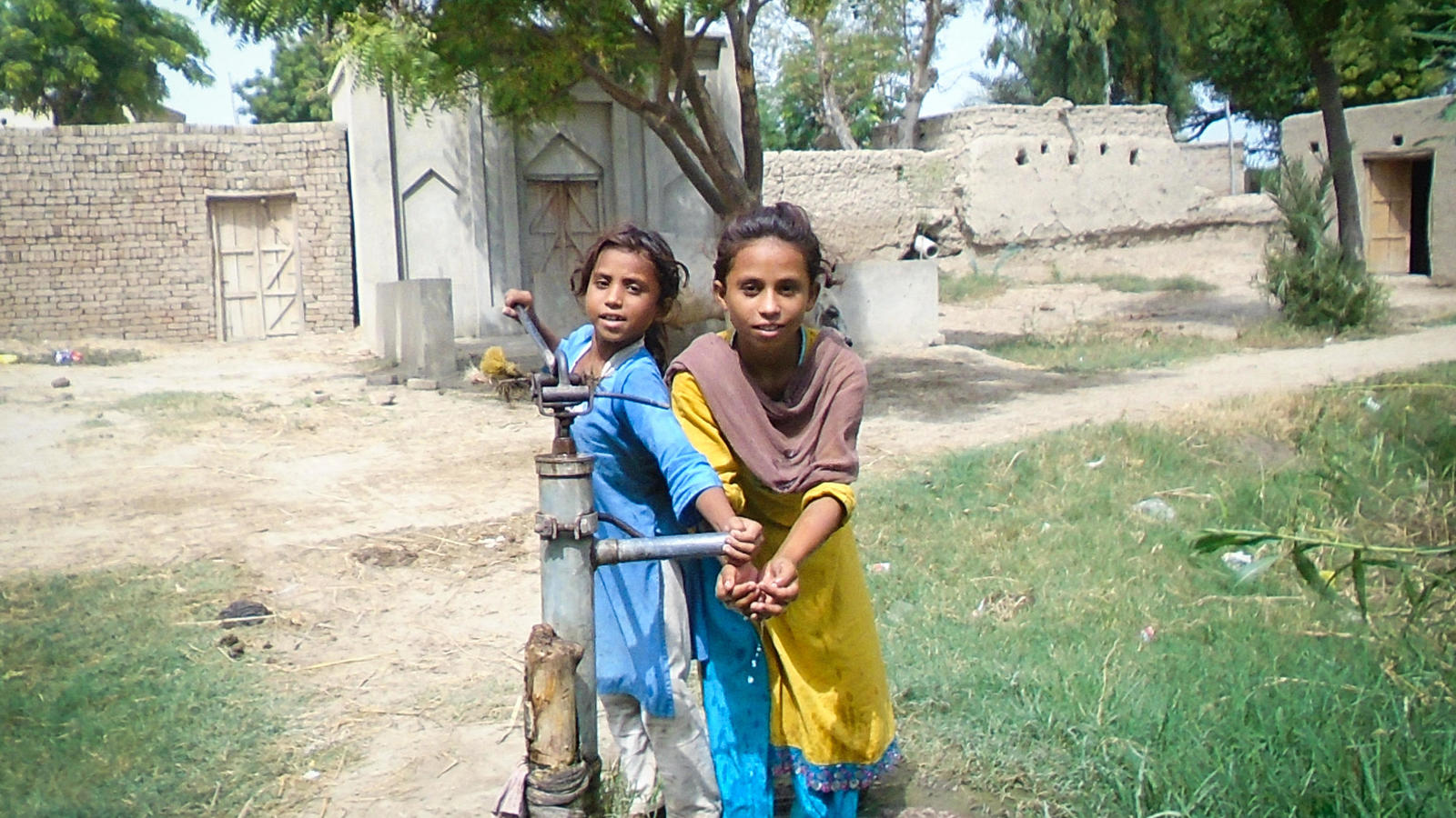 Shahana, 10, washing her hands from a pump with her friend in the village of Waan Pitafi, Pakistan.