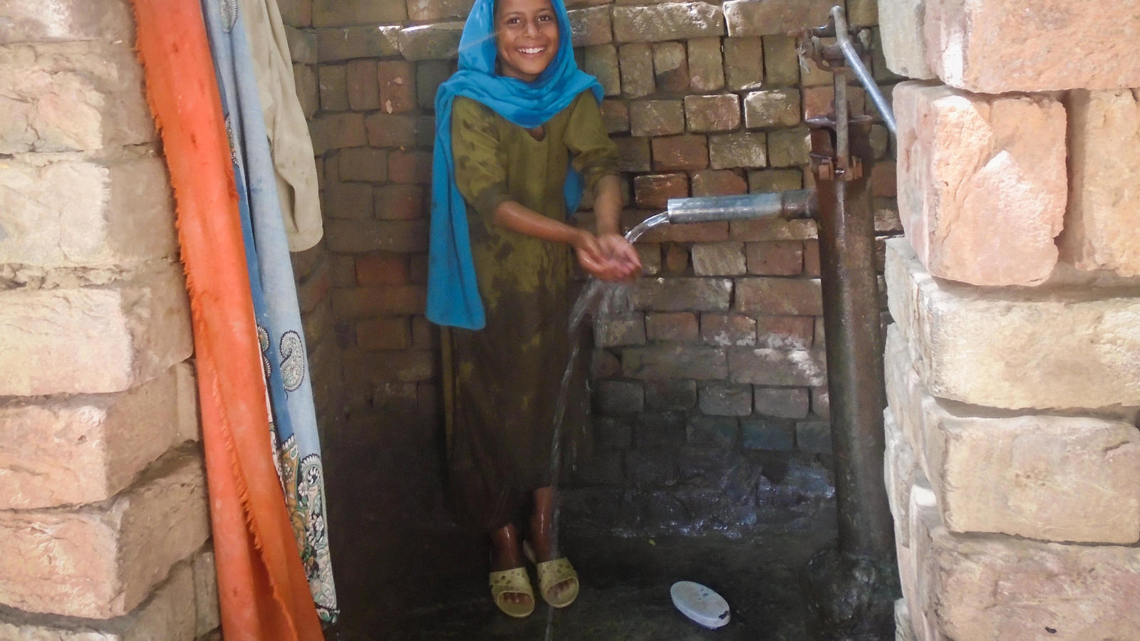 Salma, 10, washing her hands from a pump in her home in the village of Waan Pitafi, Pakistan.