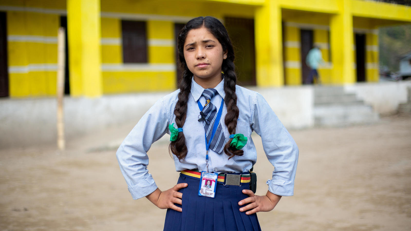 Anisha standing in front of her school in her uniform in Dolakha, Nepal, April 2019.