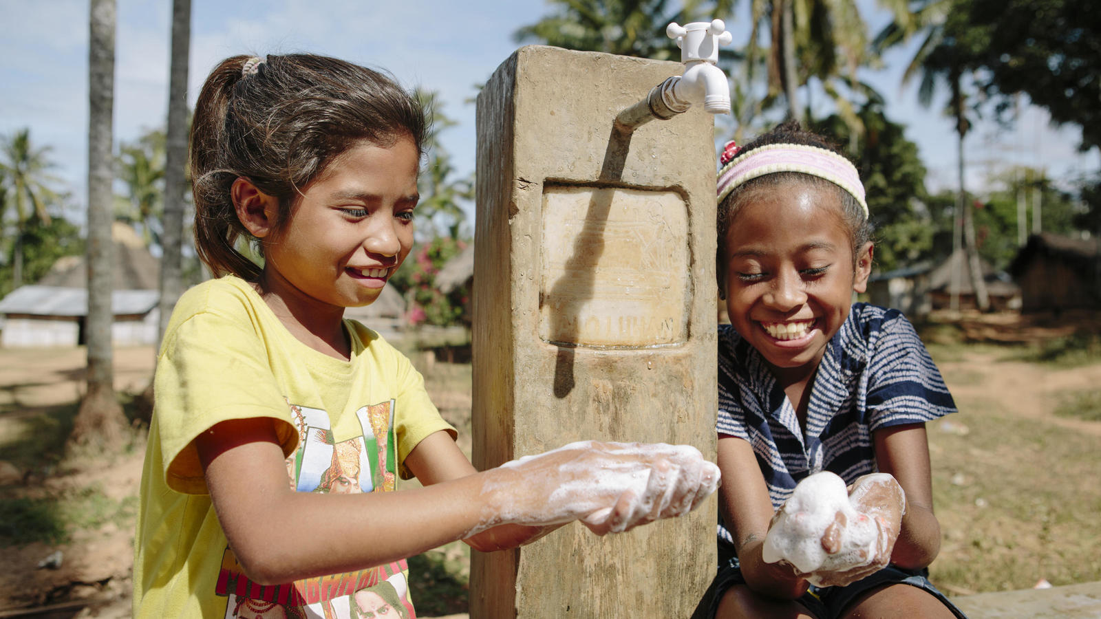 Crizonia Soares, 7, and Dircia Dos Santos, 7, handwashing at one of the new tap stands in the village of Grotu in Manufahi District, Timor-Leste, 2015
