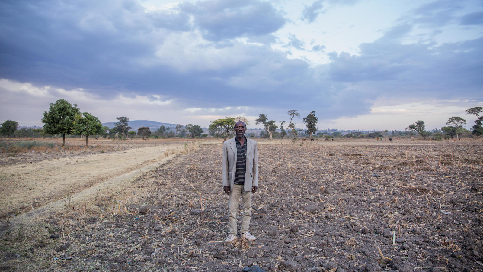 Gebre stands in a field on his farm, which he's struggling to get water to.