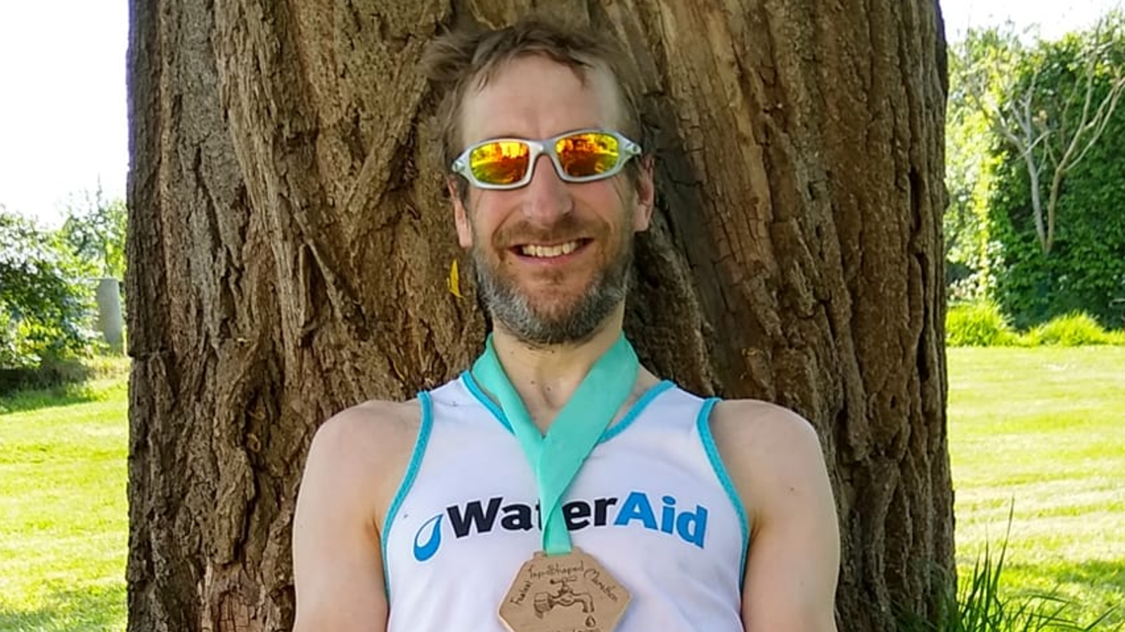 WaterAid supporter Marcus sitting under a tree with his medal, after running a marathon in his garden shaped like a tap.