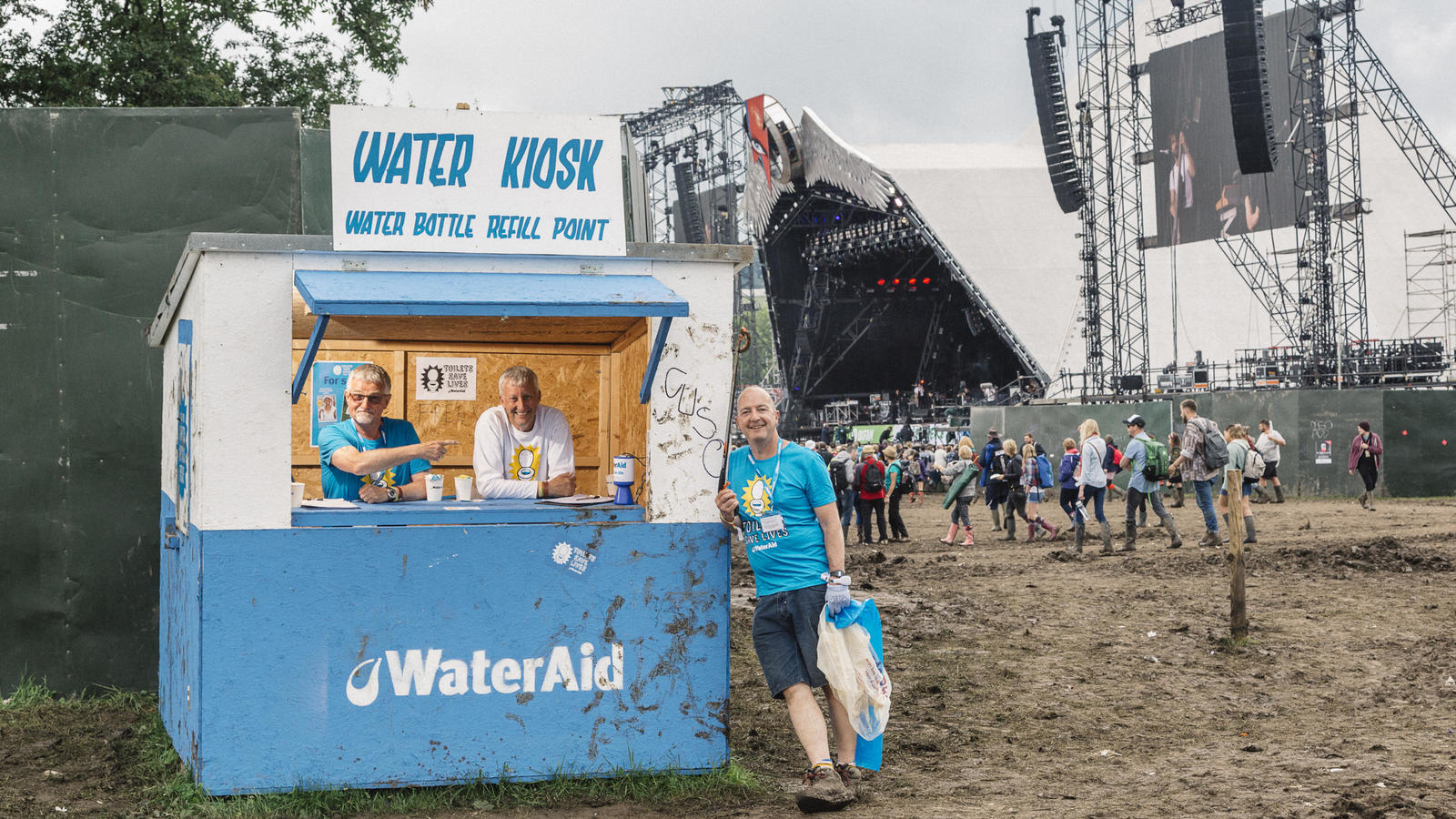 WaterAid volunteers Frank and Andrew man a WaterAid kiosk close to the Pyramid Stage at Glastonbury Festival