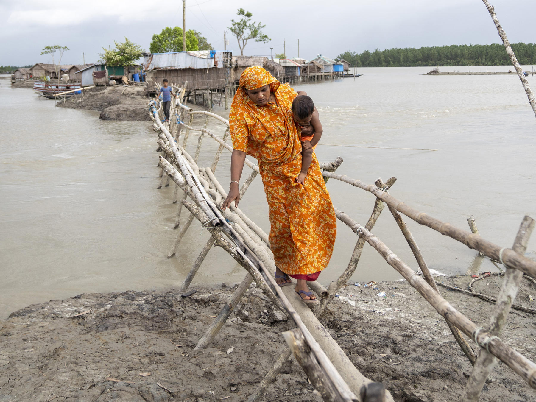 A woman walks over a bridge above tidewater, carrying her child,  Dacop, Khulna, Bangladesh.