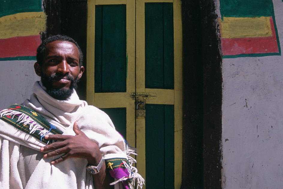 Priest Mehari stands by the front of his church in 2004, the year clean water arrived in his village in Northern Ethiopia.