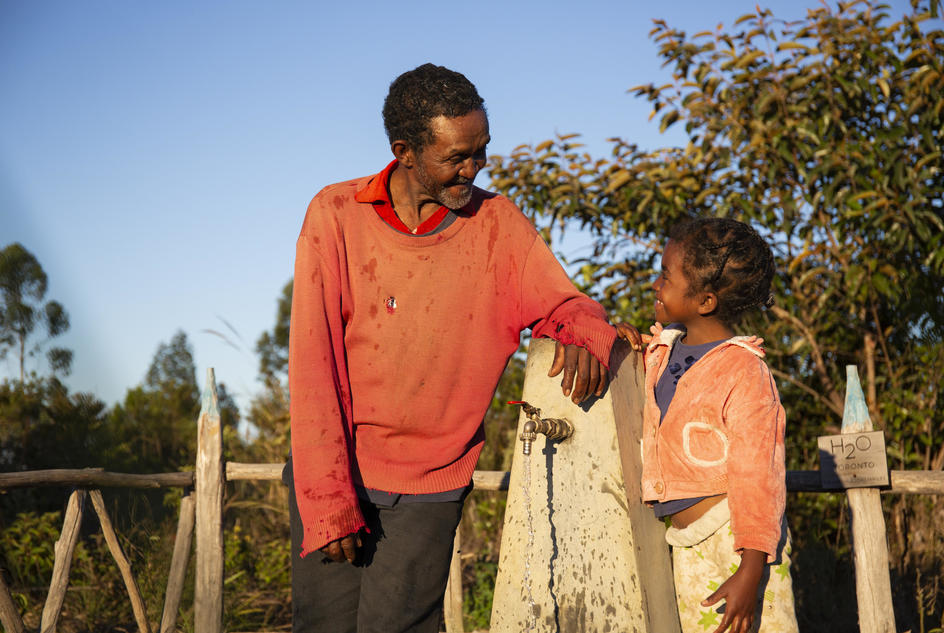 Albert Rakotoson, 67, and his granddaughter Tantely, 8, smiling as they collect water from a water point in Tsarafangitra village, Belavabary commune, Madagascar, August 2019.