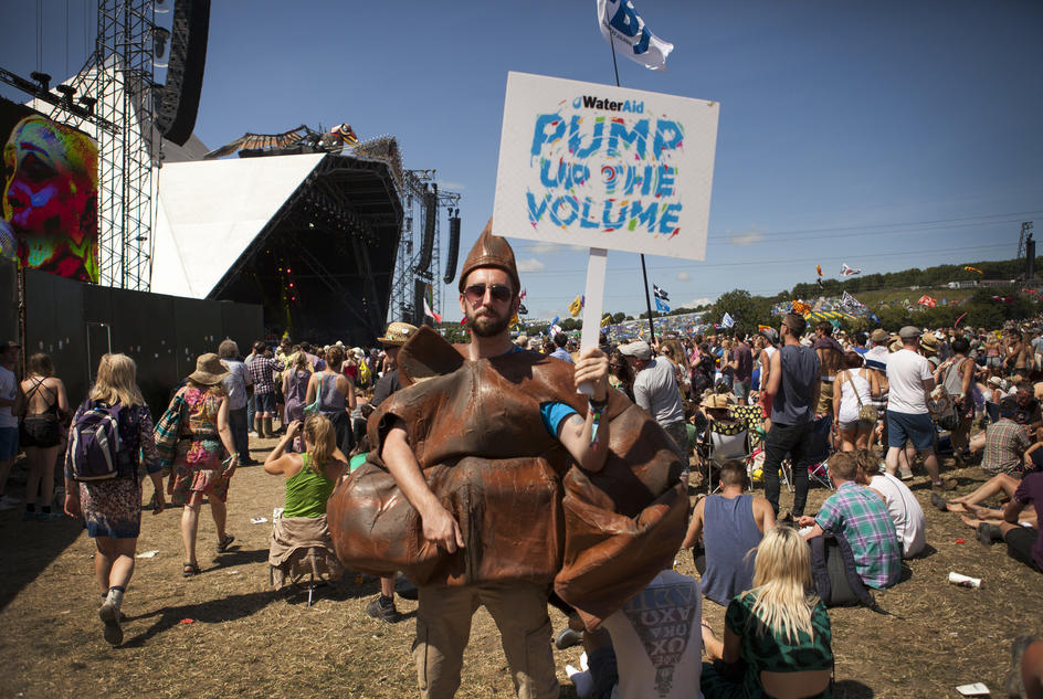 Digital Campaigner Ross Bailey wears the Poo costume and holds a Pump up the Volume sign in front of the Pyramid stage at Glastonbury 2013.
