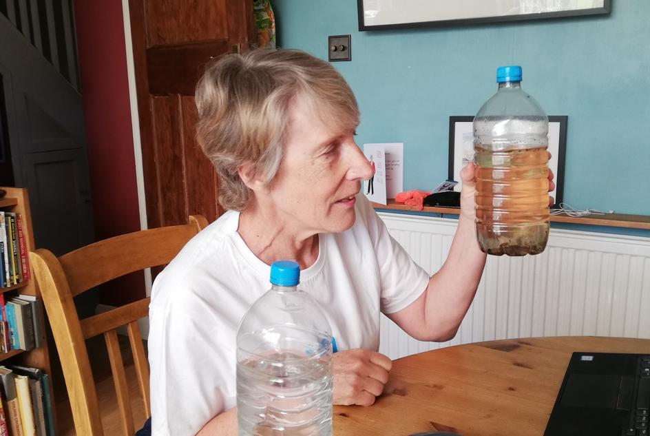 Penelope shows a bottle of dirty water to her audience, whilst delivering an online talk.