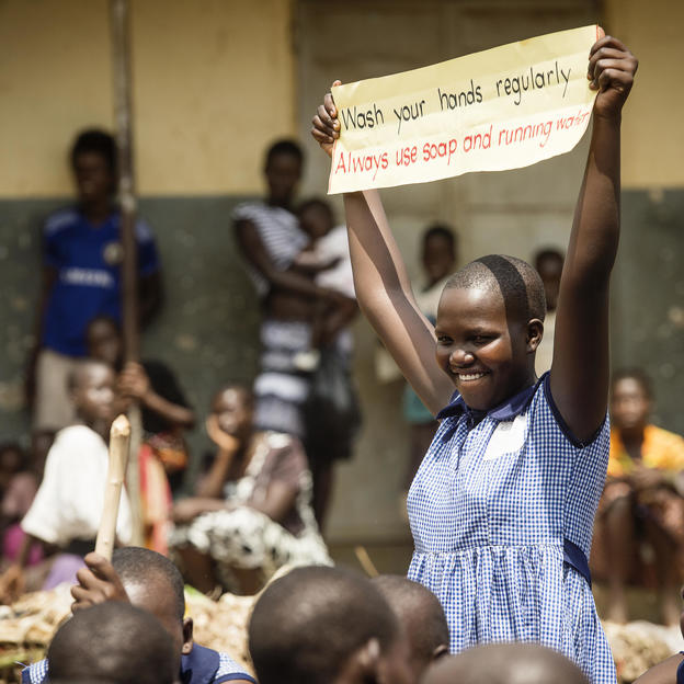WASH Club member, holds up a sign during a march to raise awareness of WASH practices, Namalu, Nakapiripirit District, Karamoja Region, Uganda, July 2017