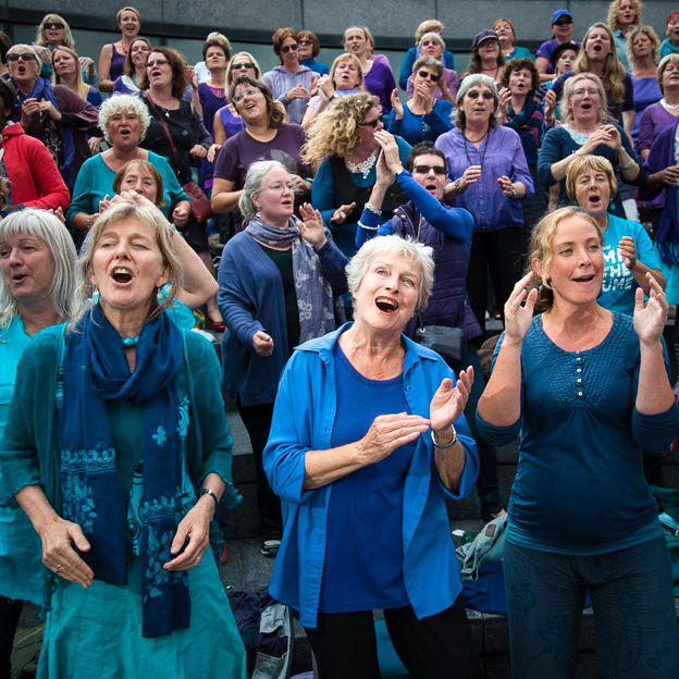 Women sing and clap at a Sing for Water event