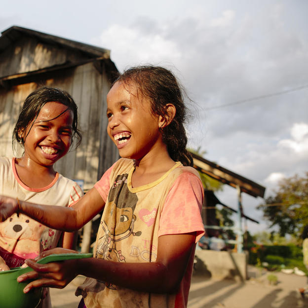 Ty and Phea play with clean water at home in Cambodia.