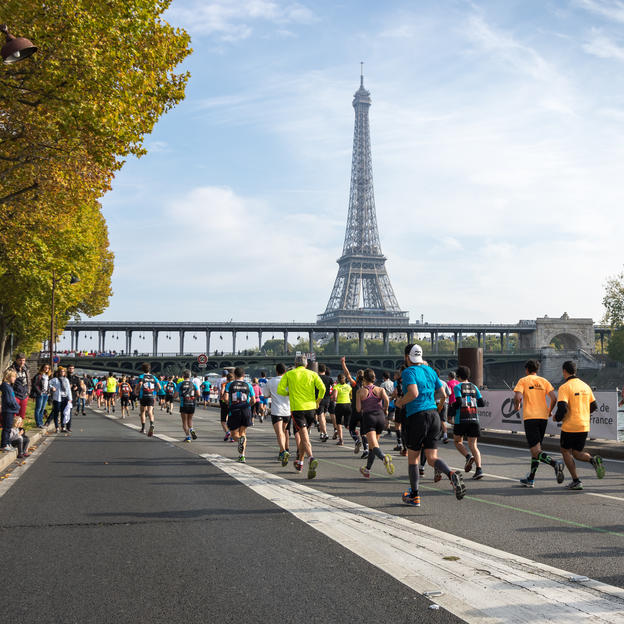 Participants in the Paris Marathon running past the Eiffel Tower
