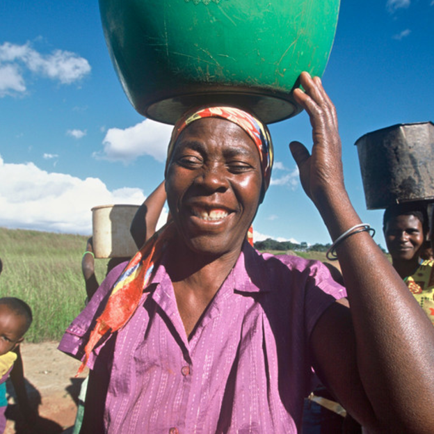 Essenati and other women carrying water they collected at the well in Mozambique