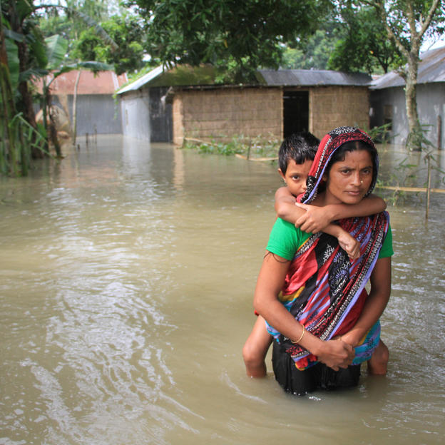 A woman carries a little boy through flood waters in Bangladesh