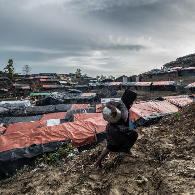 A woman carries a jar of water up a muddy slope in Balukhali refugee camp, where thousands of Rohingyas who fled violence in Myanmar are now living.