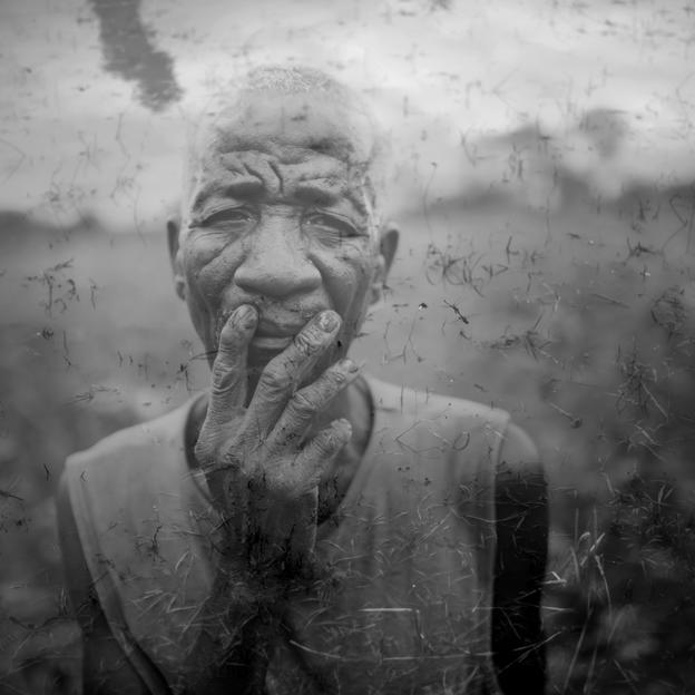 Joao Magaissa, a farmer in his 70's, overlayed on an image of a puddle of murky water formed after the first day of the rainy season in Niassa, Mozambique,