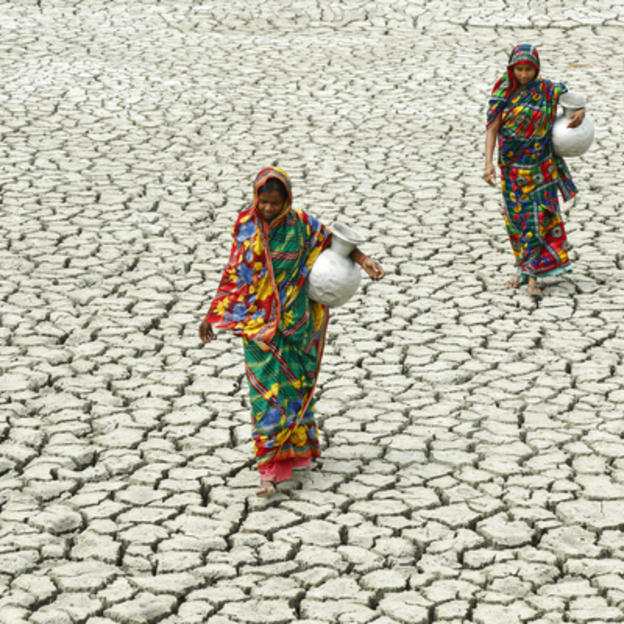 Village women walk on cracked ground, towards a pond to collect water.