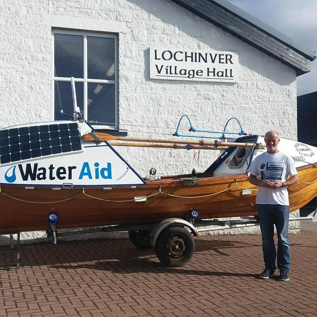 Duncan standing next to his self-made boat