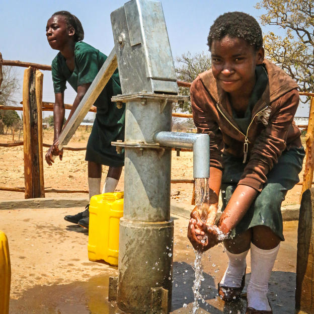 A girl collects water at her school in Zambia.