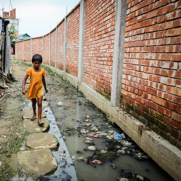 A child walks through the road, which has no drainage facility and all wastes from hanging toilet go directly to the road, Gojariapara, Gazipur, Bangladesh, April 2017