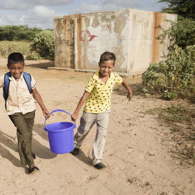 Two students of Wayuuma'ana School bring back a bucket of clean water they just filled up at the deposit near the school in Wayuuma'ana, Colombia, 2017.