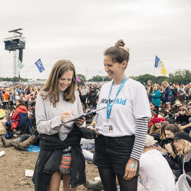 A WaterAid staff member collects signatures for the 2016 WaterAid 'Toilets Save Lives' Campaign. The campaign aims to raise awareness of the 2.3bn people worldwide who don't have access to a clean toilet. Festivalgoers at the 2016 Glastonbury Festival were encouraged to sign a petition urging the UN to ensure that this situation will be resolved by 2030.