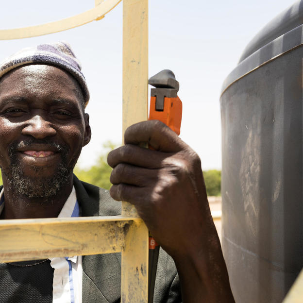 """When I go up the water tower, I remember when we were waiting for this facility for a long time; now we've got it, I stand up there and I'm very happy."" Souleymane Diallo, 56, climbs up the water tower to fix a fault. Souleymane is one of four water mechanics trained by WaterAid. Samabogo village, Mali"
