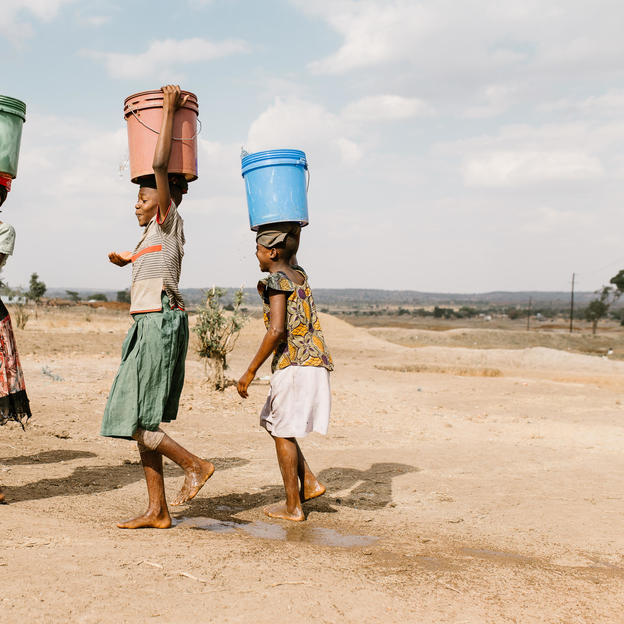 Girls carry water away from a privately owned shallow well on the edge of Nyarugusu. This is the closest water source to Nyarugusu Dispensary, a 15-min drive away; the well runs low in the dry season and is subject to contamination in the rainy season. Nyarugusu, Tanzania, September 2017.