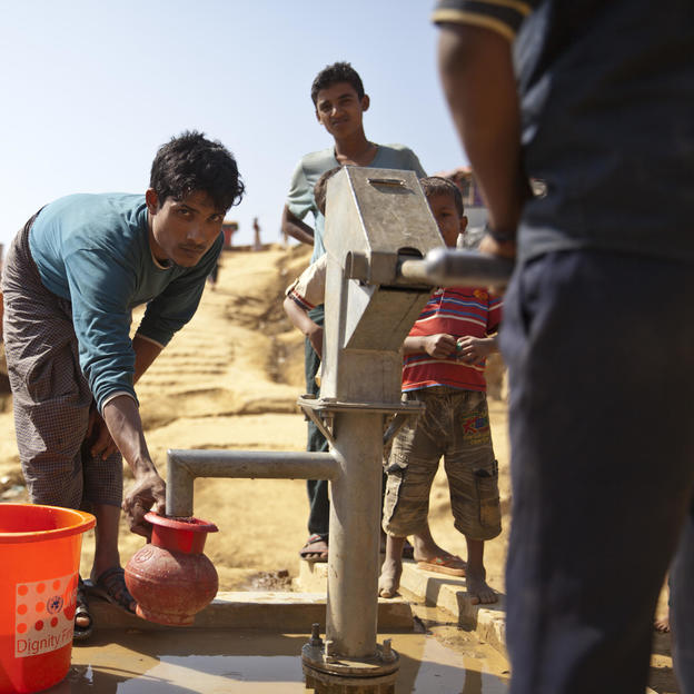 A Rohingya man collects clean water from a tube well installed in the Kutupalong refugee camp in Bangladesh