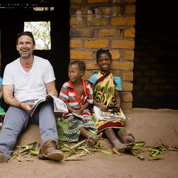 Dougray Scott, WaterAid Ambassador, sits with (L-R) Anilbazino, 7, Lateone, 8, Erica, 8, and Clara, 10, outside their classroom at the M'Mele Primary School, M'Mele Village, Cuamba District, Niassa Province, Mozambique. May 2017.